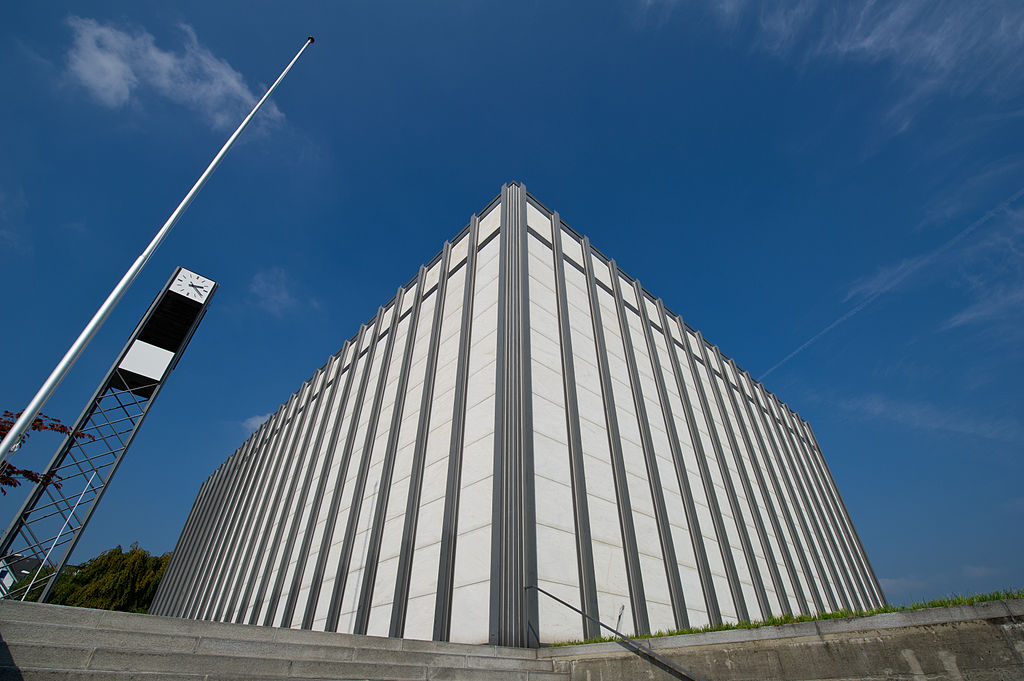 Color photograph of two outside walls of the church taken from ground level against a blue sky. From this perspective, the church looks like a ship and the corner between the walls has the appearance of its bow. The church's freestanding clock tower to the left of the church and two flag poles seem to be pointing to heaven.
